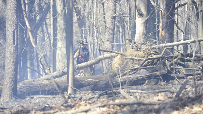 A firefighter works to stop a brush fire in South Burlington on April 16, 2016