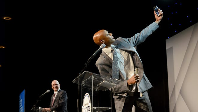 James F. Byrnes High School's Malik Epps takes a Snapchat photograph of his Boys Cross Country Runner of the Year award at The Greenville News Upstate Sports Awards on Monday.
