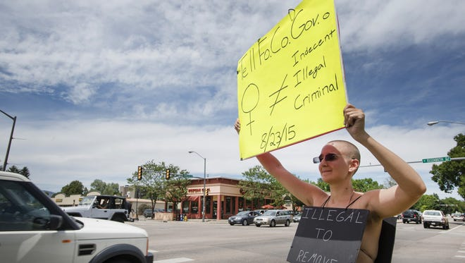 Brittiany Hoagland protests Fort Collins indecency laws Aug. 6, 2015, as traffic passes by at the intersection of South Shields and West Elizabeth streets. Hoagland says the language in the city law is sexist and unconstitutional against women and the transgender community.