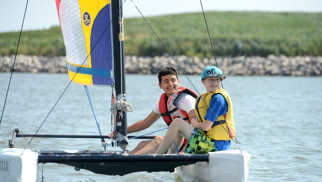 Maliq Mendez, 13, left, and Neil Rand, 12, learn to sail with help from Green Bay Sail and Paddle instructors Tuesday near South Bay Marina.