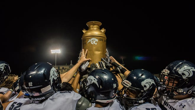 The Piedra Vista football team lifts the milk can trophy after beating rival Farmington on Friday at Hutchison Stadium.