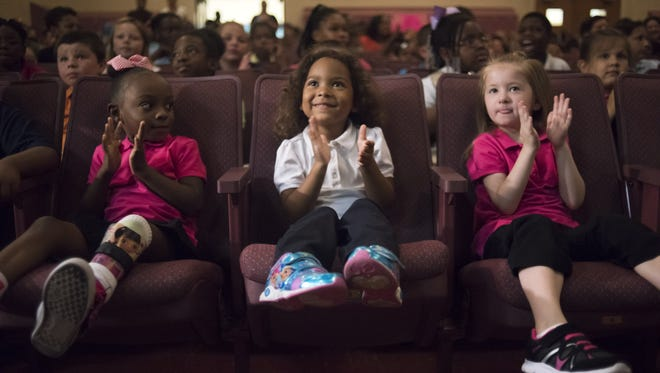Rosalynn Smith, 5, center, applauds during the Kids in Need Foundation giveaway at Freeman Elementary in Flint on Tuesday. The nonprofit group is giving backpacks filled with school supplies to the district's 5,500 students.