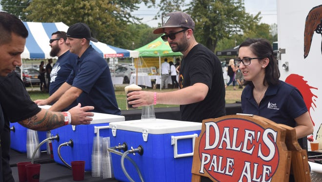 Bartenders with Craft New York serve craft brews to thirsty festival-goers at Taste of New Paltz Sunday at the Ulster County Fairgrounds.