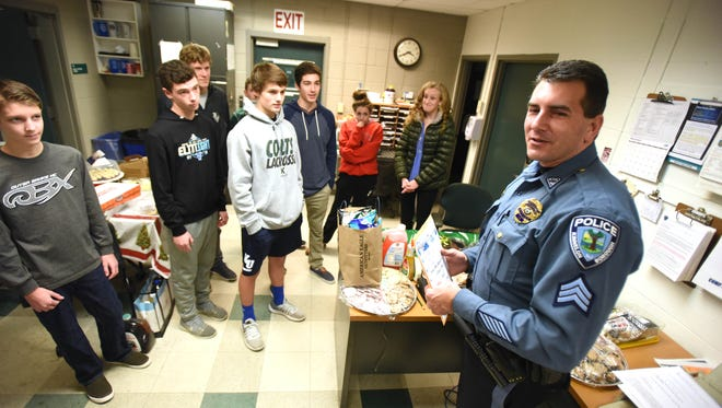 Sgt. Chris Carbone greets members of Kinnelon High School's Future Business Leaders of America club and teacher Anna Ellington who brought a couple of holiday meals for the 14 or so cops scheduled to work on Christmas Eve and Christmas Day.