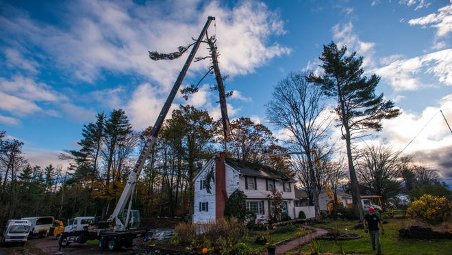 Crews work to remove trees that fell on a home off Vermont 15 in Essex just east of Allen Martin Drive Monday morning, Oct. 30, 2017. Powerful winds felled trees, blocking roads and cutting power to thousands.