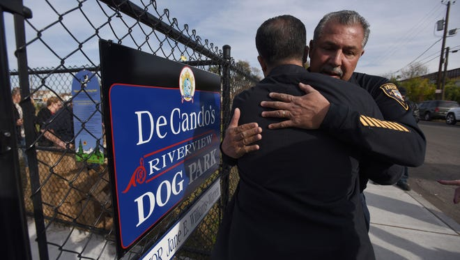 """John DeCando gets a hug from a friend in front of the new """"John DeCando Dog Park,"""" which was named in his honor."""