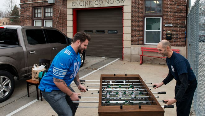 Lions offensive tackle plays foosball with a Detroit firefighter. The game was one of many items donated to four DFD firehouses by Ford, the Lions and the Leary Firefighters Foundation.