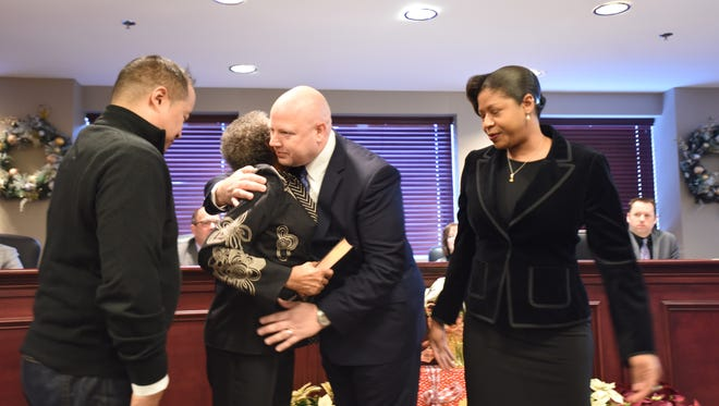 Newly elected mayor William Hauser being congratulated by family members.