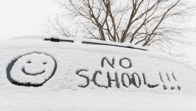 Someone wrote NO SCHOOL!!!  with a smiley face emoji in the freshly fallen snow on the side window of their car in the morning. They must be happy because they do not have to go to school because of the snowfall.