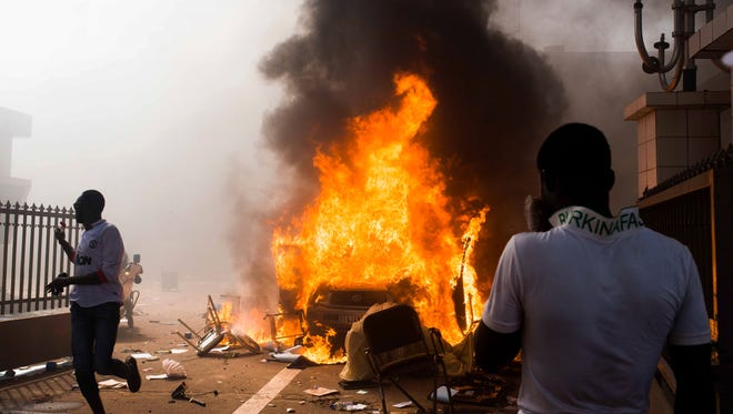 A car burns after being set alight by protesters outside the parliament building in Burkina Faso on Oct. 30, 2014.