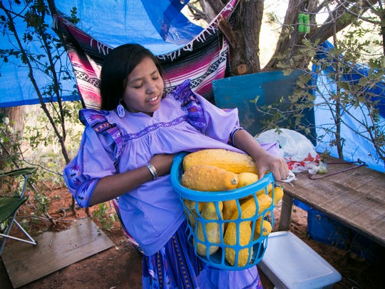 Kaila grabs a basket of gourds at the family's camp site during preparations for the Sunrise Ceremony.