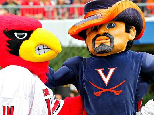 The Louisville Cardinals' mascot and the Virginia Cavaliers' mascot stand together on the sidelines during their teams' game at Scott Stadium. The Cavaliers won 23-21.  Sept. 13, 2014