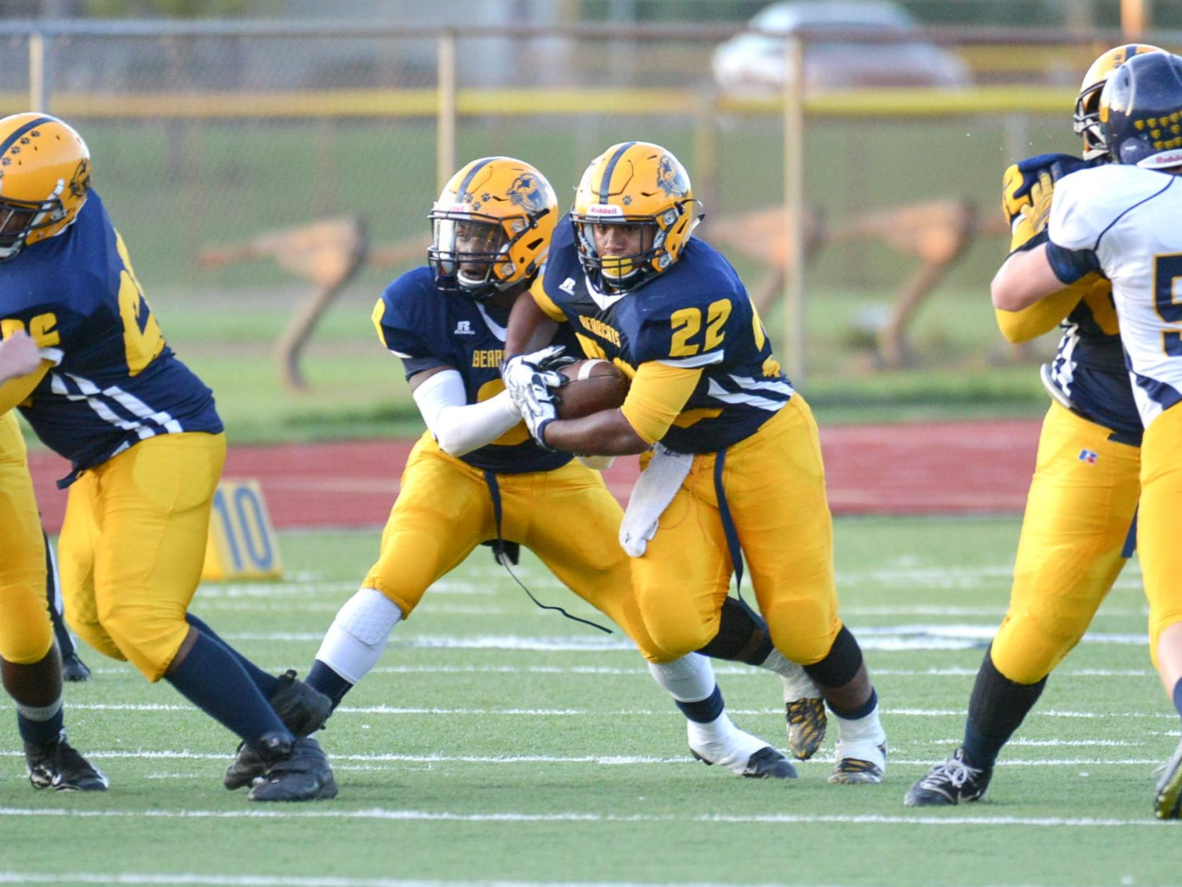 Battle Creek Central RB Carlos Parks secures the handoff from QB Dennis Watson and he rushes for positive yards Friday night.