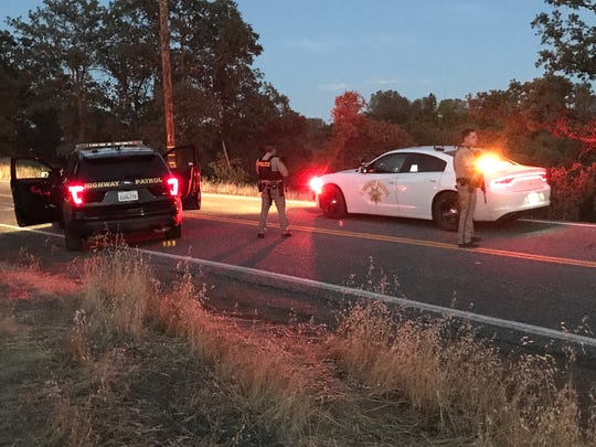 California Highway Patrol officers block Hooker Creek Road east of Interstate 5 on Saturday night where a subject possibly with an AK-47 assault rifle was in a field.