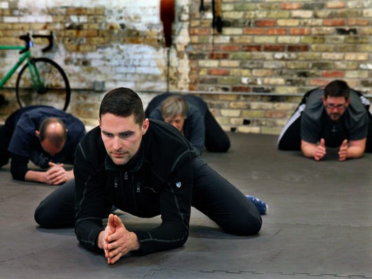 Superb Health trainer and owner Nick Lynch does a  pelvis stretch with his class during the cool down, meditation and breathing techniques portion of his Bay View class in February 2018. Lynch teaches the Functionally Fit class that incorporates meditation.