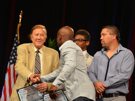 Boxing champ shakes hands with former Raiders coach Tom Flores at the Sports Heroes Luncheon, benefitting the Boys & Girls Club of Coachella Valley, at the Hyatt Regency Indian Wells Resort & Spa on Thursday, Feb. 19, 2015.