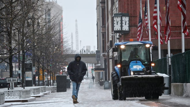 A man walks past a snow truck on Woodward Ave. on Wednesday, February 24, 2016, in Detroit, MI.