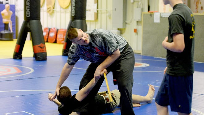 Wilson Bunn pins down head instructor David Pestoff to help Micaiah Bilerey, 12, with his form during a kids advanced class at Dojoku Martial Arts on Thursday, April 28, 2016. Bunn is a second degree black belt and certified instructor at the school as well as an officer with the Asheville Police Department.