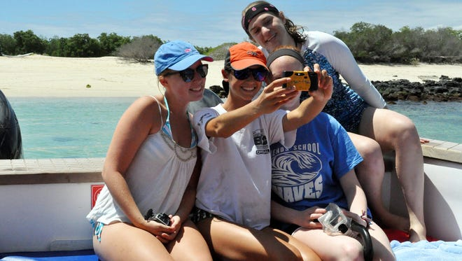A group of American high school students, from left,  Isabela Gettier, Elizabeth Thomas, Hannah Whitt Linsly  and Stephanie Kirby posing for a group selfie on a trip to the Galapagos. Young travelers say they enjoy taking selfies to preserve and curate travel memories while sharing experiences with friends. But some older travelers worry that spending too much time on social media can be a distraction from enjoying and learning about a place.