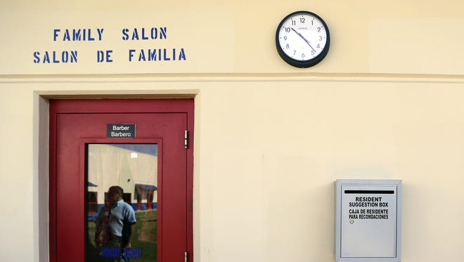 """In this July 31, 2014, file photo, a suggestion box hangs on the wall outside of the hair salon at the Karnes County Residential Center, in Karnes City, Texas. Homeland Security Secretary Jeh Johnson says federal officials are making """"substantial changes"""" to end the long-term detention of migrant families who are being held mainly at two large facilities in Texas."""