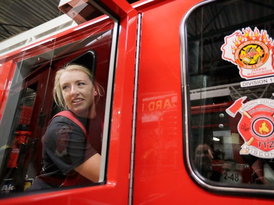Probationary firefighter Sam Hackl loads her gear into a fire engine for a training exercise Tuesday at the Howard Fire Station. Nationally, women comprise only 7 percent of all firefighters, according to the National Fire Protection Association.