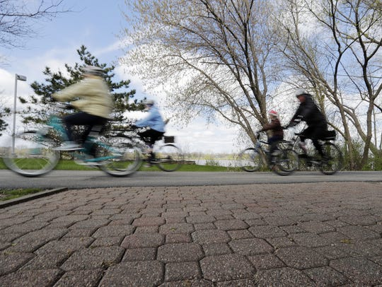 Cyclists bike along the Fox River Trail  in De Pere.