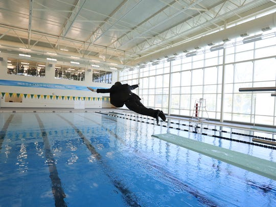St. Norbert President Tom Kunkel dives into the new swimming pool Friday following the dedication ceremony for the Mulva Family Fitness and Sports Center at St. Norbert College. The Mulvas were the lead donors in a $26 million renovation and expansion which includes a new swimming pool and a fitness center.