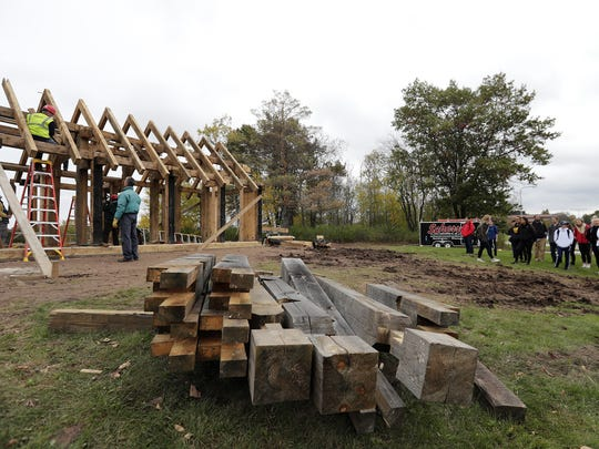 University of Wisconsin-Green Bay students watch as a replica of a Viking-age house is reconstructed on the UWGB campus on Thursday. The house was donated by Owen and Elspeth Christianson who built it on their property in Stratford in 2011.