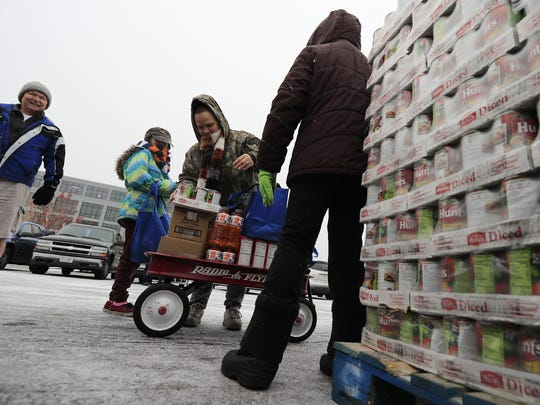 Gina Uphill of Denmark and her daughter Theresa, 10, pick up food at a Feeding America Eastern Wisconsin mobile food pantry in the Titletown Brewing parking lot on Saturday in Green Bay. Volunteers assisted with the distribution of food to community members in need as part of the USA TODAY NETWORK-Wisconsin's annual Stock the Shelves Campaign, which raises money for local food pantries and awareness of the issue of food insecurity.