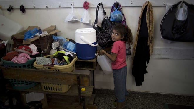 A Palestinian girl fills a container with water at a classroom of a United Nations-run school in Gaza City on September 13, 2014 one day before children go back to school.