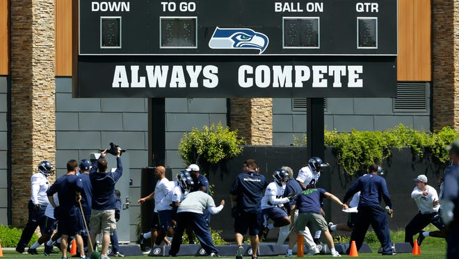 Seattle Seahawks rookie players run a drill under the scoreboard at the team's practice facility in Renton, Wash., during NFL football rookie minicamp, Friday, May 8, 2015, in Renton, Wash.