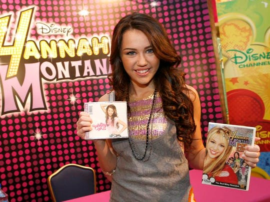 "Miley Cyrus poses with her first solo CD, ""Hannah Montana 2/Meet Miley Cyrus,"" and the DVD, ""Hannah Montana Pop Star Profile"" in 2007, a year after she first played Miley Stewart/Hannah Montana on Disney Channel."