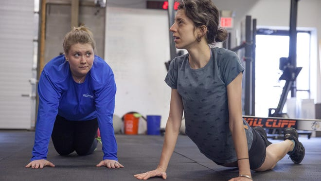 Free Press staffers Haley Dover, left, and Emilie Stigliani, do push-ups at Mountain Trail CrossFit in Colchester on Friday morning.