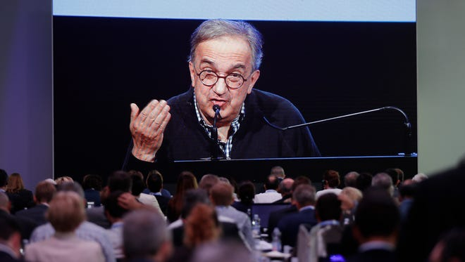 Journalists watch a giant screen as Fiat Chrysler CEO Sergio Marchionne speaks during the 'Capital market day' at the FCA headquarters in Balocco, Italy, Friday, June 1, 2018. Fiat Chrysler CEO Sergio Marchionne is outlining his business plan for the automaker's next five years in his last big presentation to investors before retiring next year. (AP Photo/Luca Bruno)