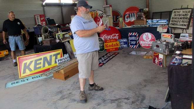 Michael Lord, right, shows the world some of the wares for sale Aug. 15 during Bouckville Online. He was broadcasting live from the pavilion behind Gallery Antiques and Collectibles on Route 20 in Bouckville, owned by John Mancino, left.