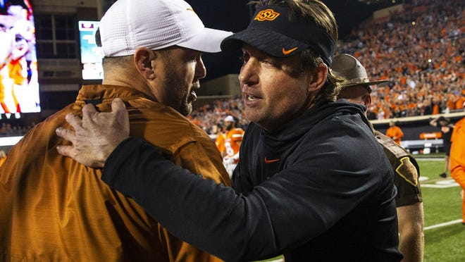 Texas coach Tom Herman, left, meets with Oklahoma State's Mike Gundy after the Cowboys' 38-35 win in 2018 in Stillwater. The Horns will visit Oklahoma State again Saturday.