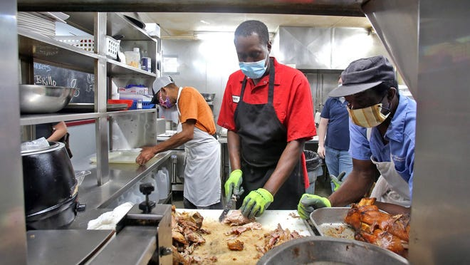 Employees wear masks while preparing orders at Bridges Barbecue in Shelby on Thursday.