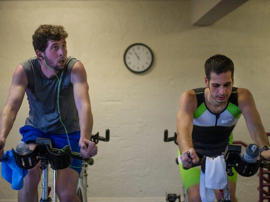 John Thiel of Evansville, left, and Alex Narang of Newburgh, Ind., compete in the YMCA Indoor Triathlon at the Downtown Evansville location Sunday morning.