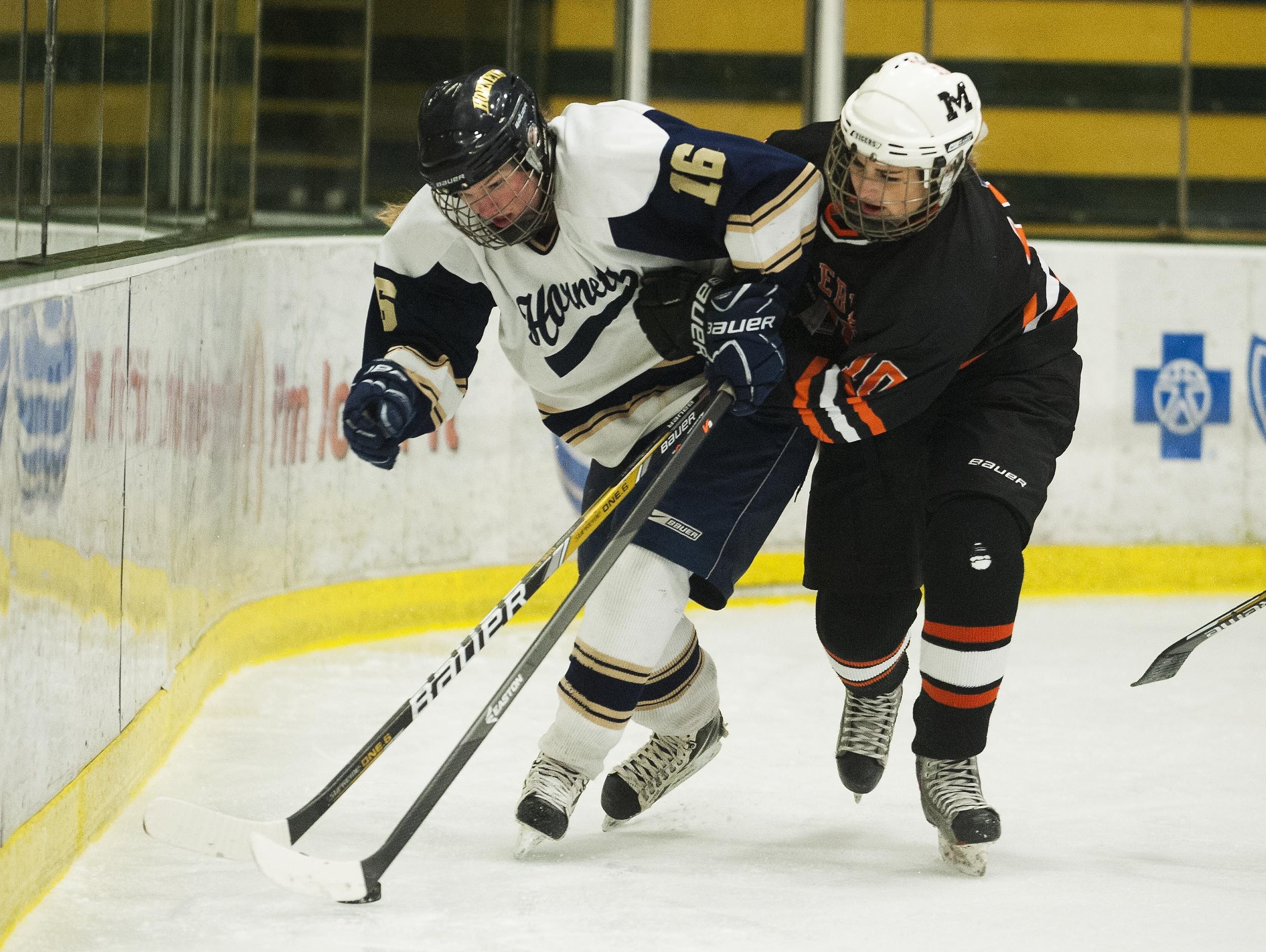 Middlebury's Allison White (10) battles for the puck with Essex's Avery MacGillivray (16) during the Division I high school girls hockey championship last season.