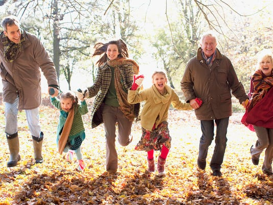 Extended family running in park in autumn