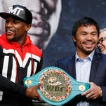 Boxers Floyd Mayweather Jr., left, and Manny Pacquiao pose with a WBC belt during a press conference Wednesday, April 29, 2015, in Las Vegas. Mayweather will face Pacquiao in a welterweight title fight in Las Vegas on May 2.