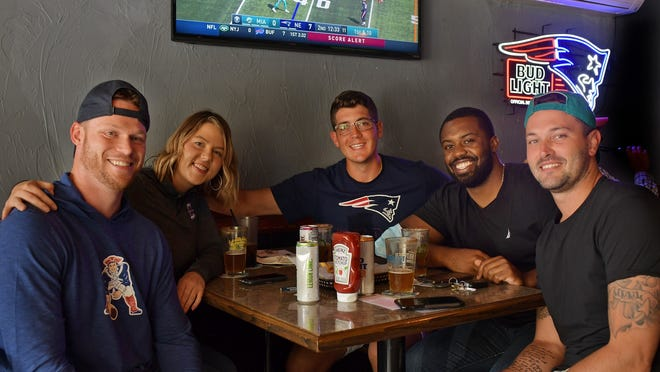 Friends from Assumption College (except for Sarah Kupec) from left, Erik Abramson, Sarah Kupec, Alex Gusha, Quinton Preston and Sonny Dillinger comment on their favorite NFL teams while watching the New England Patriots game on TV at the Banner Bar and Grille on Sunday.
