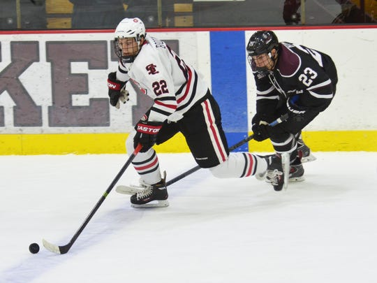 St. Cloud State's Jonny Brodzinski (22) carries the puck with Union's Tyler HInes (23) in pursuit.
