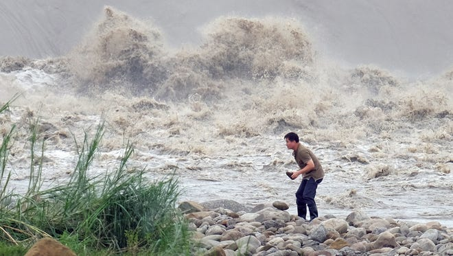 A local resident collects stones from the Xindian river after Typhoon Dujuan hit New Taipei City on Sept. 29, 2015.