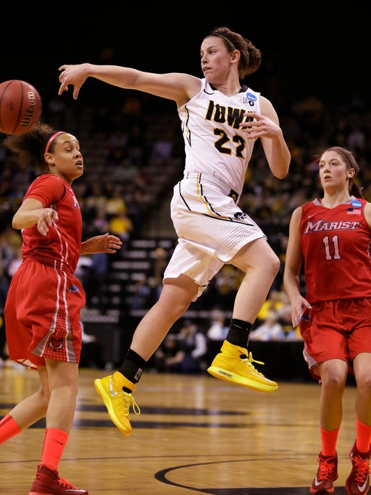 Iowa guard Samantha Logic, center, passes between Marist defenders Sydney Coffey, left, and Leanne Ockenden, right, during the first half of an NCAA tournament first-round women's college basketball game, Sunday, March 23, 2014, in Iowa City, Iowa. (AP Photo/Charlie Neibergall)