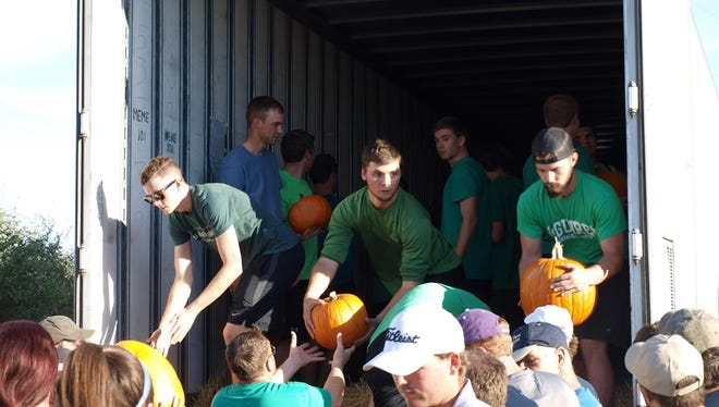 Members of the Gamma Sigma Phi men�s social club at Abilene Christian University haul pumpkins out of a trailer at the Disabilities Resources pumpkin patch.