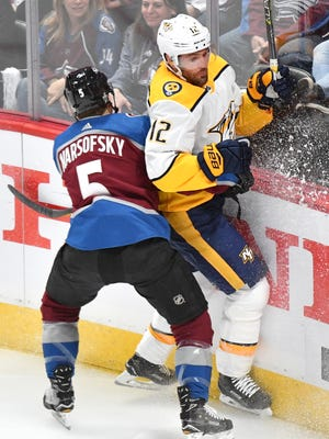Nashville Predators center Mike Fisher (12) and Colorado Avalanche defenseman David Warsofsky (5) battle along the boards during the first period of game 3 of the first round NHL Stanley Cup Playoffs at the Pepsi Center, Monday, April 16, 2018, in Denver, Colo.