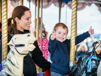 A happy mother and son are riding on a carousel together, smiling and having fun at an amusement park.  The boy holds two thumbs up.