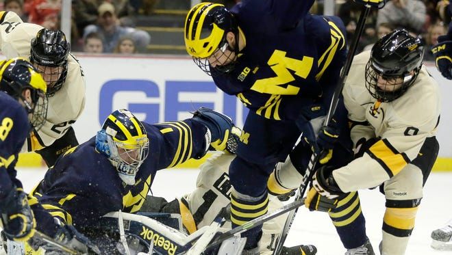 Michigan's Kevin Lohan (24) tries to clear the puck after goalie Steve Racine (1) stopped a shot by Michigan Tech's Alex Gillies, right, during the second period of the Great Lakes Invitational NCAA college hockey game, Sunday at Joe Louis Arena.