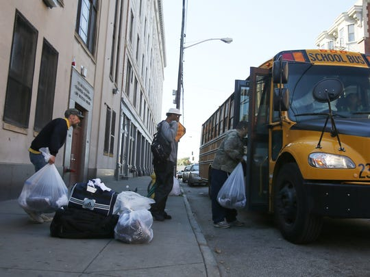 Drop Inn Center residents board a bus to move to the